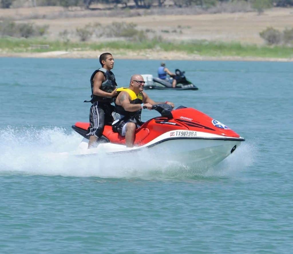 Demonstrates a passenger riding a jet ski while standing up