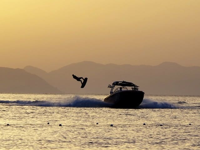 Wakeboarding at sunset. Wakeboards are towed around 25 mph but the boats can often reach 50 mph