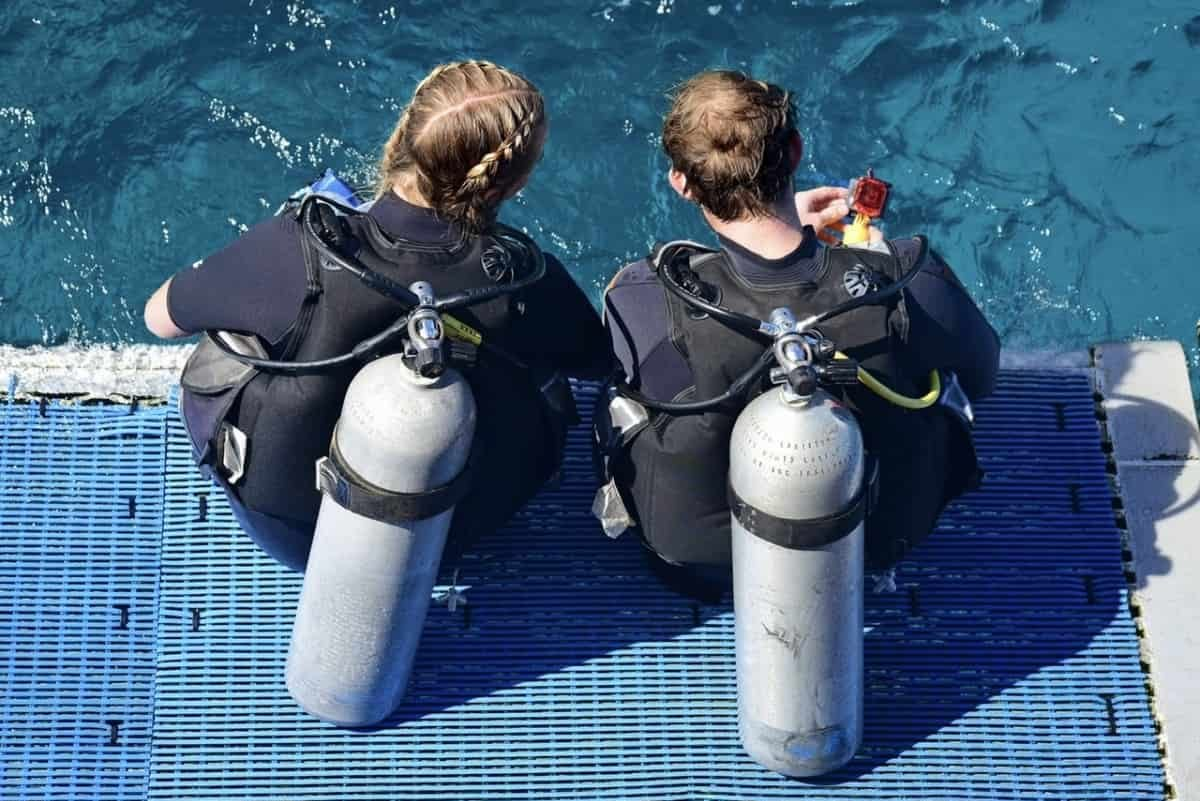 2 scuba divers in gear sitting on entry deck of boat
