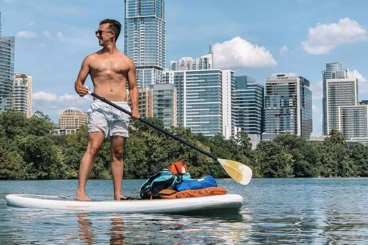 Paddle boarding is fun for multiple reasons. This guy is paddle boarding right in a downtown area on his local river
