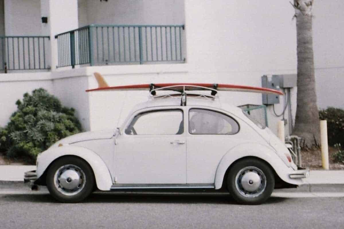Roof rack on a white Volkswagen Beetle with a paddle board on top