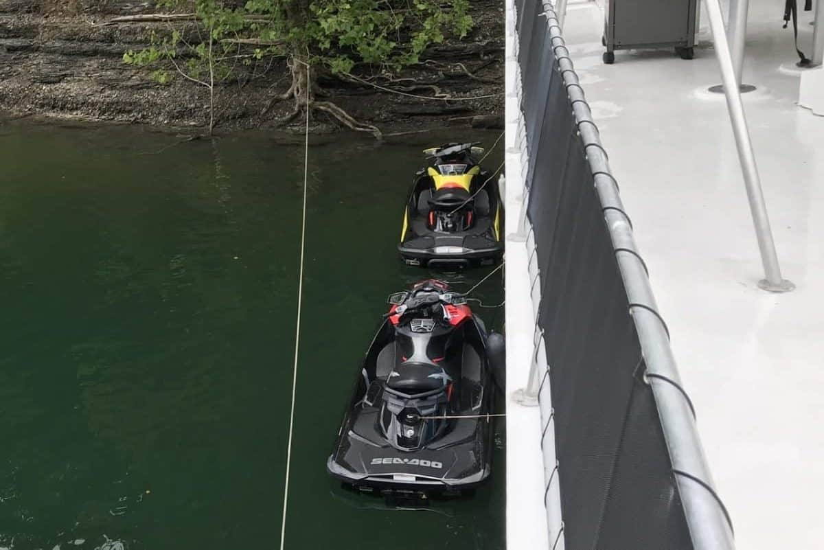 2 sea doos docked to a houseboat on a lake