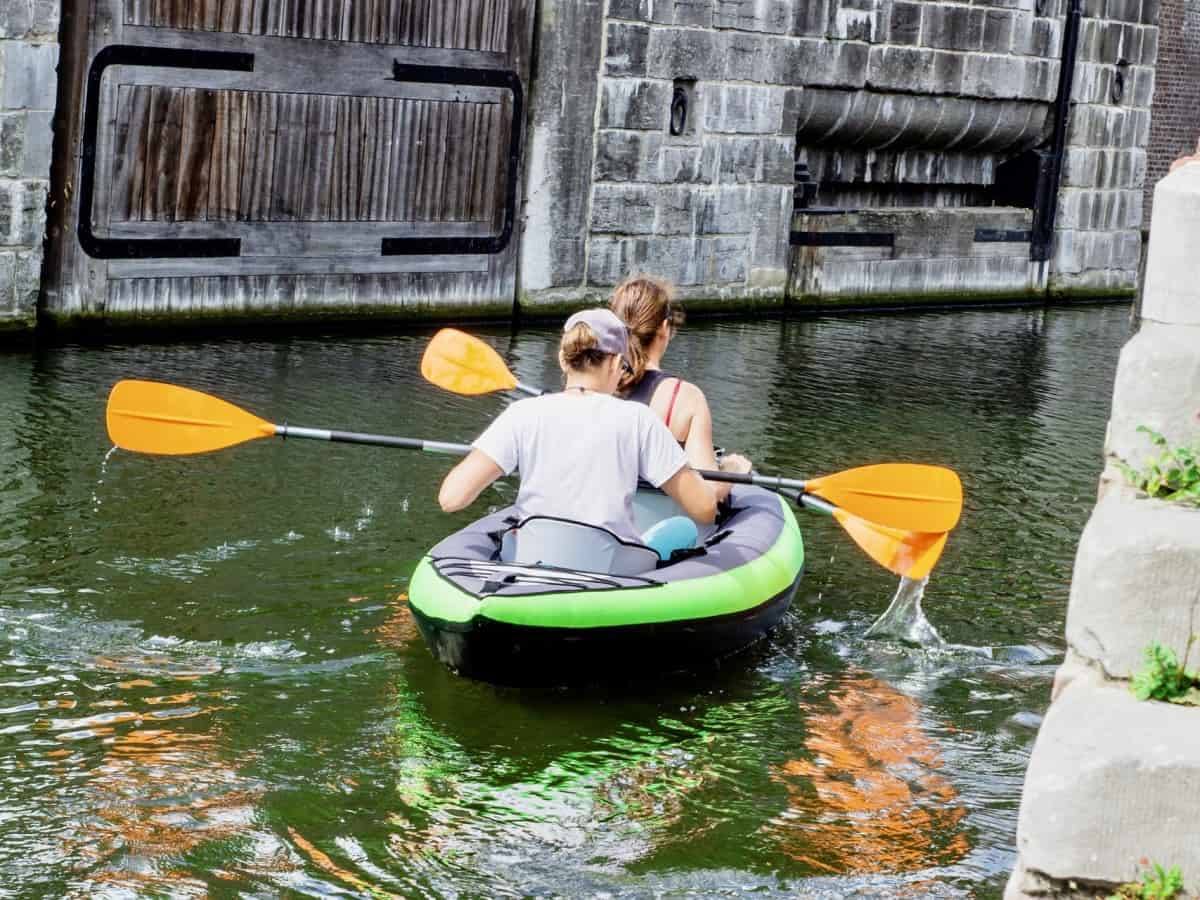 Photo of 2 people in green kayak on a canal