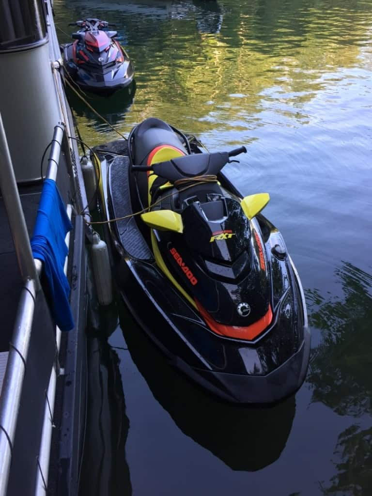 Docking a jet ski takes time and caution. Here we have Sea-Doos tied to a houseboat