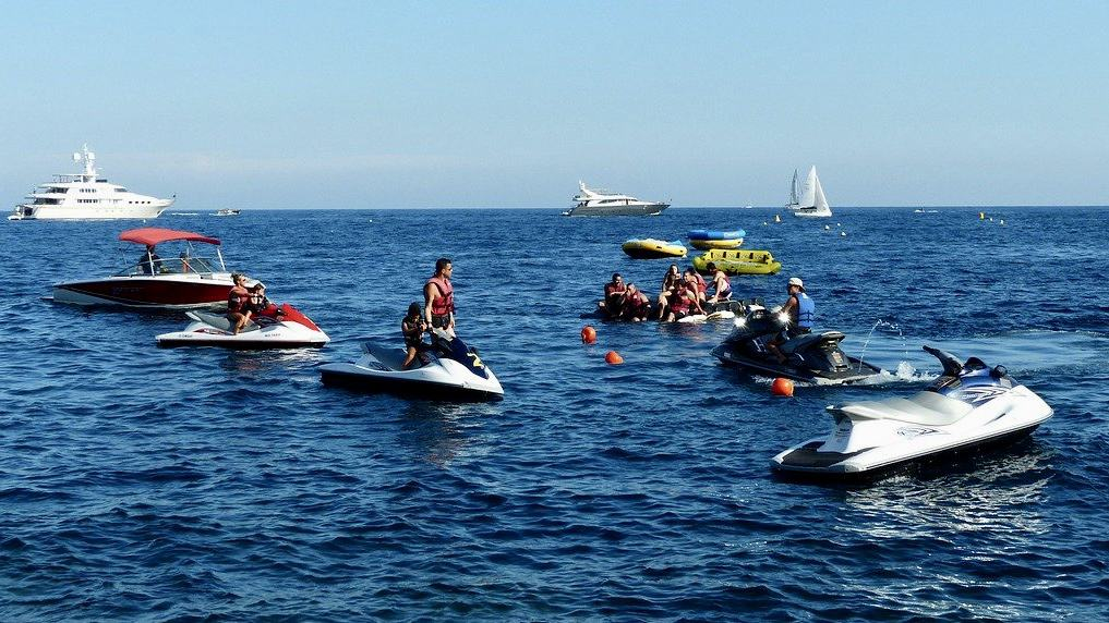 Group of jet skis in ocean with larger boats in distance