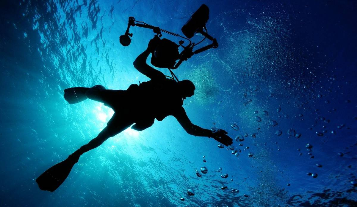 Diver with a cumbersome ull camera and lighting that can be replaced by snorkeling with a GoPro camera