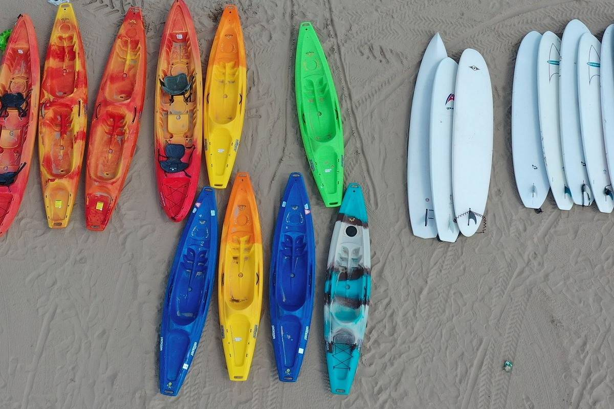 Kayaks and paddle boards lying on beach. kayaks will be faster