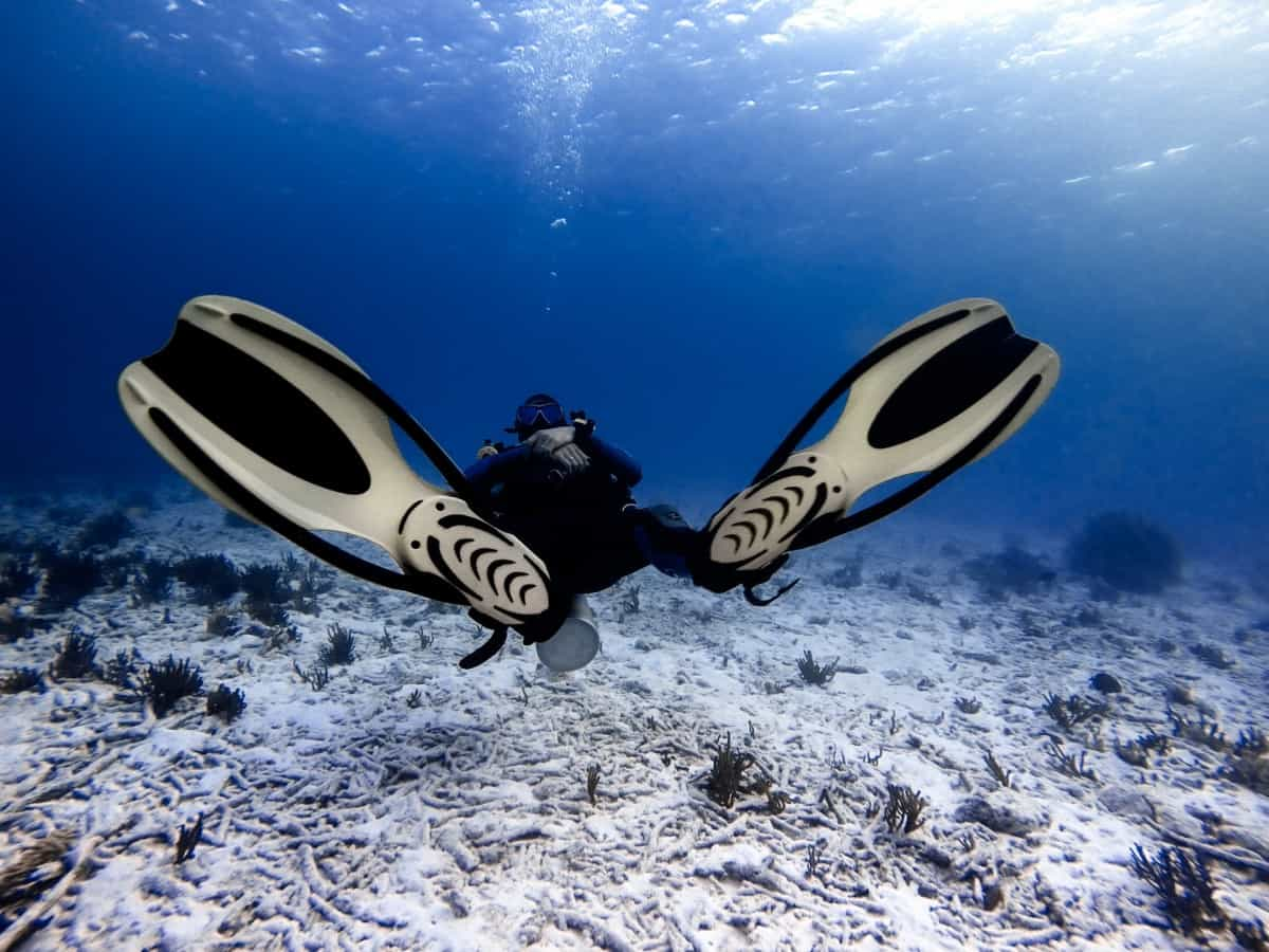 Scuba diver lying on sand with fins up