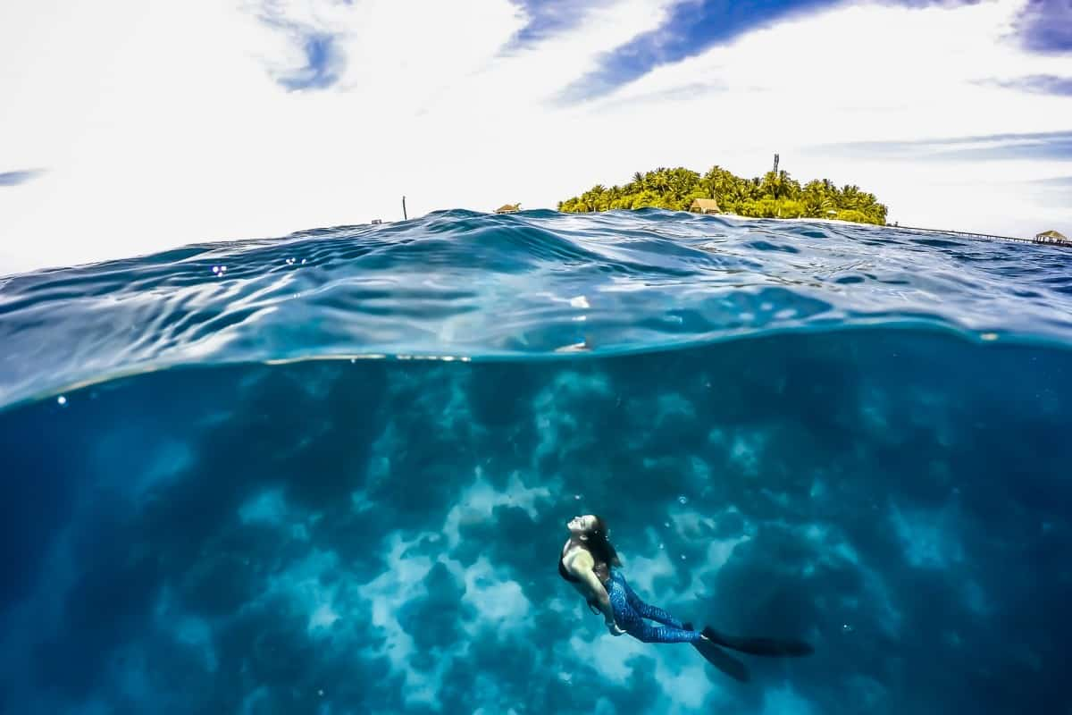 Photo at surface of ocean with freediver under and an island in top half