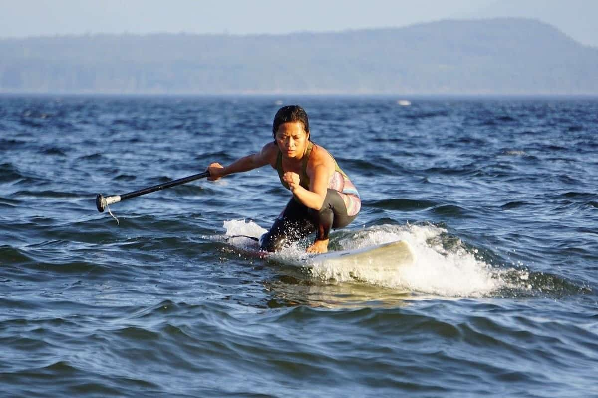 female using paddle board to surf