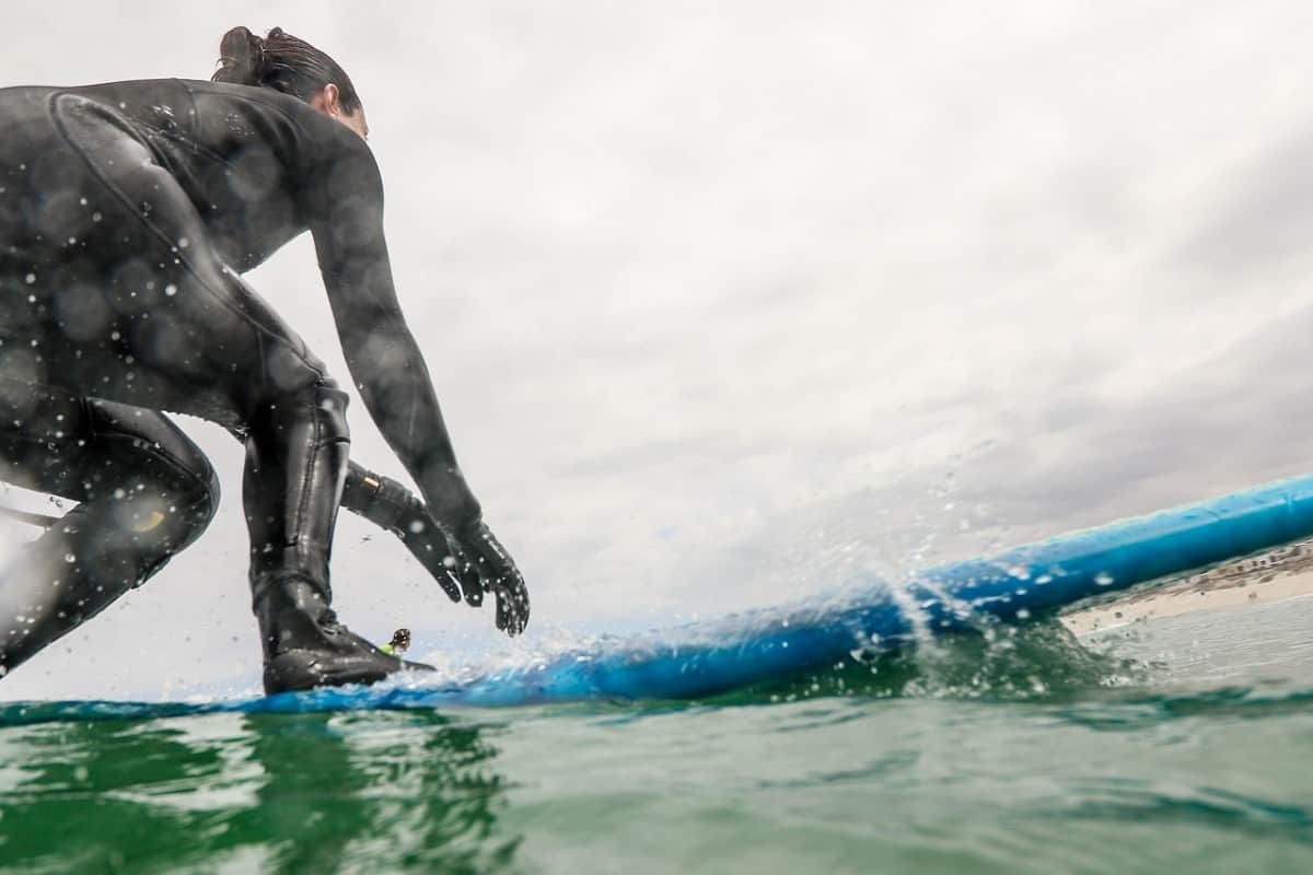 Surfing wetsuit worn while surfing, design is different than scuba wetsuits